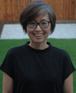 Portrait of Reiko Tanaka. Reiko is standing in her garden. She is smiling and wearing a black top and blue and black glasses.