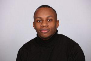 Portrait of De-Shaine Murray. De-Shaine is sat in front of a white backdrop, he is wearing a black turtle neck