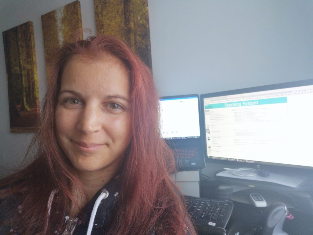"""Photo of Edit working from home. Edit is sat in front of two PC monitors. She is smiling and wearing a grey hoodie with white ties. The screen on the right hand side says """"Teaching System"""""""