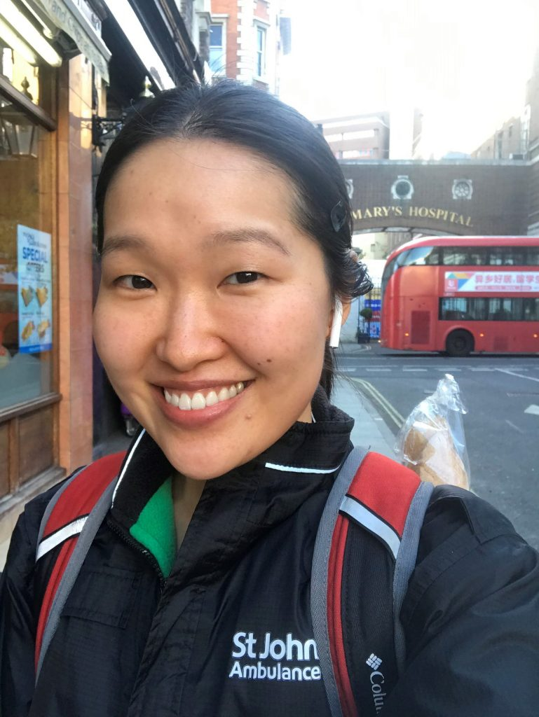 "Selfie by Julia Sun. Julia is standing outside smiling, her hair is pulled into a ponytail. She is wearing a black jacket with a green lining and the words ""St Johns Ambulance"" are embroidered on the left hand side. She is wearing a black and red backpack. There is a red double decker bus in the background"