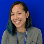 Portrait of Julie Hoang. Julie is sat smiling in front of a blue backdrop. She is wearing a grey jumper over a white shirt and black jeans.