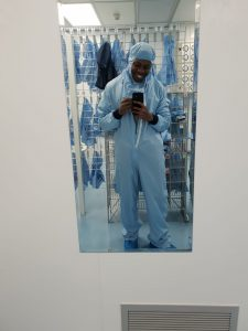 A mirror selfie in a Bioengineering lab by De-Shaine. He is wearing full Personal Protective Equipment including a jumpsuit with a hood