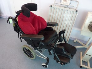 A typical carer-propelled bespoke wheelchair including moulded foam seat and seat tilting mechanism