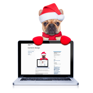Small dog wearing a santa hat holding a laptop displaying the Content Design blog.