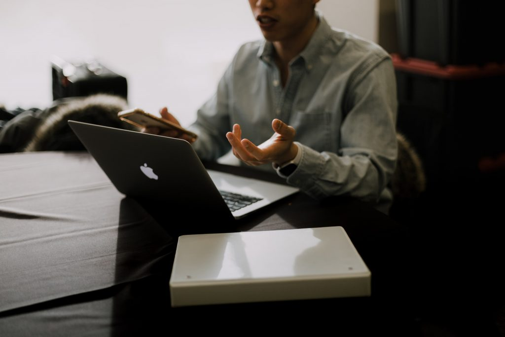 A person talking into a laptop