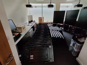 A room full of monitors stacked on the ground