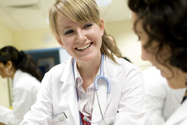 A photograph of a female doctor smiling in discussion with another female doctor.