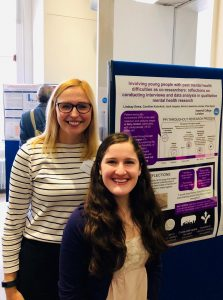 A photograph of Lindsay presenting a poster of her research with one of the young people she worked with.