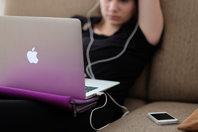 A girl at an apple mac laptop on a sofa with earphones in