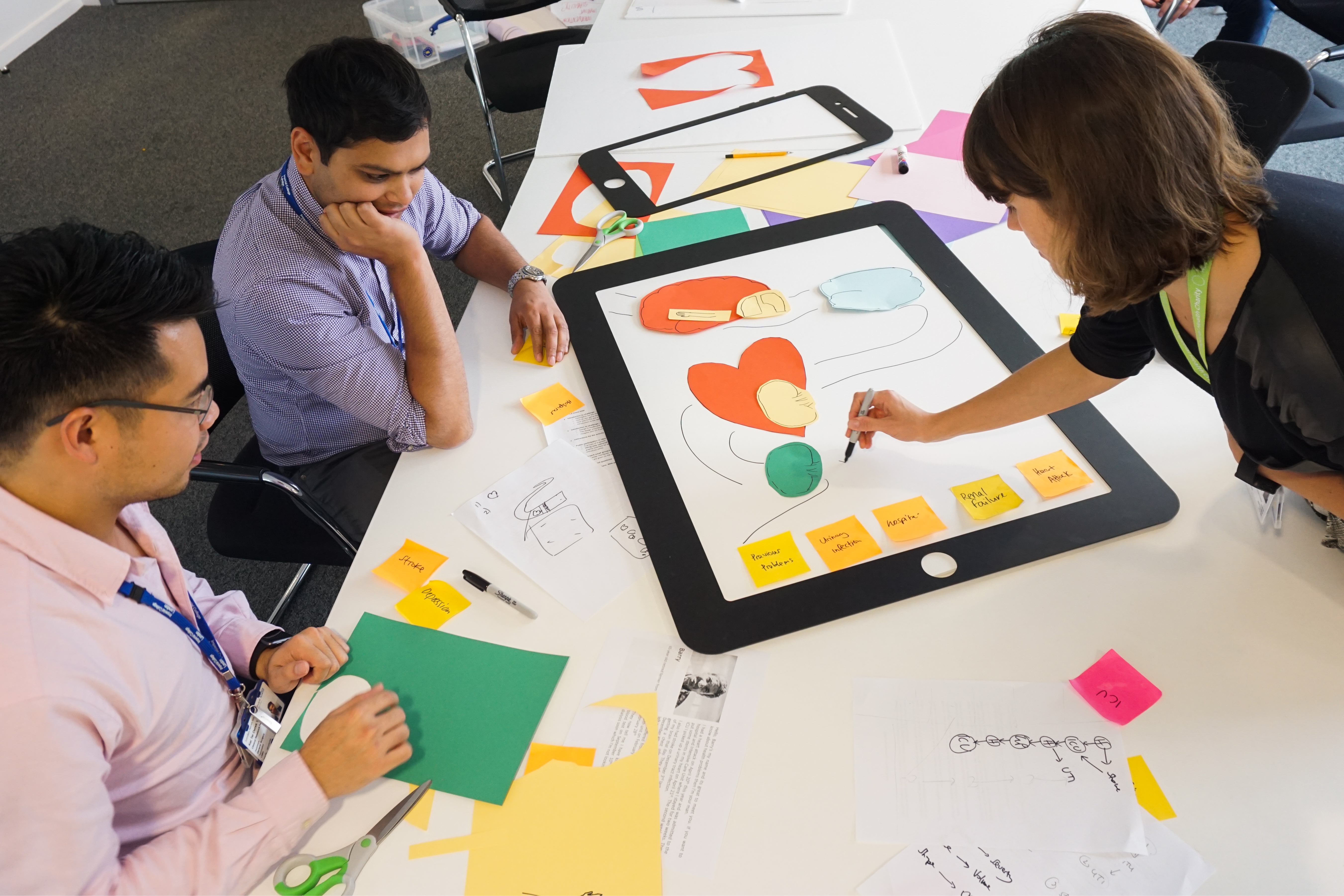 People drawing on coloured paper at a design workshop