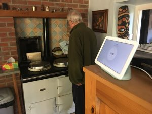 A man cooking with a smart home device behind him on the kitchen counter
