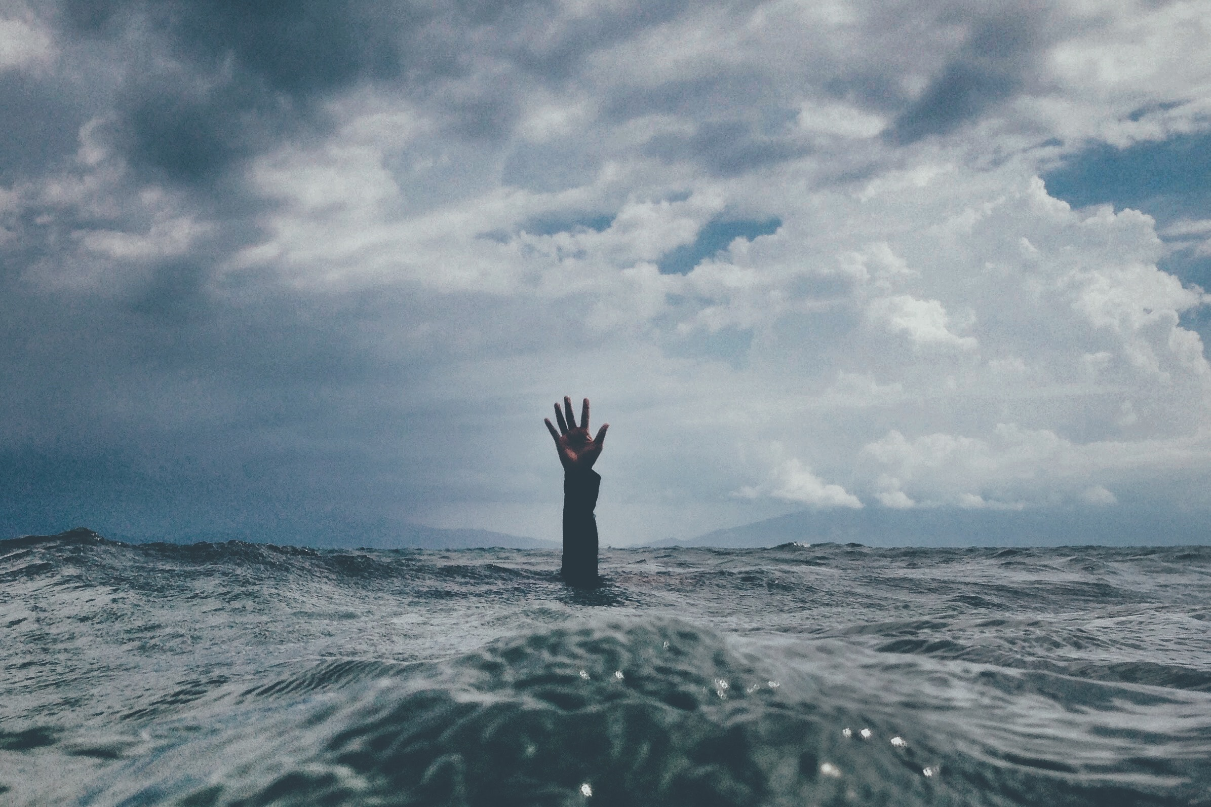 A hand emerging out of open water