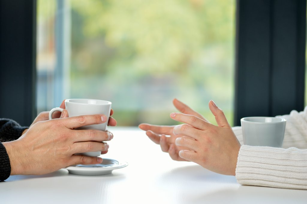 Hands of two people taking with coffee