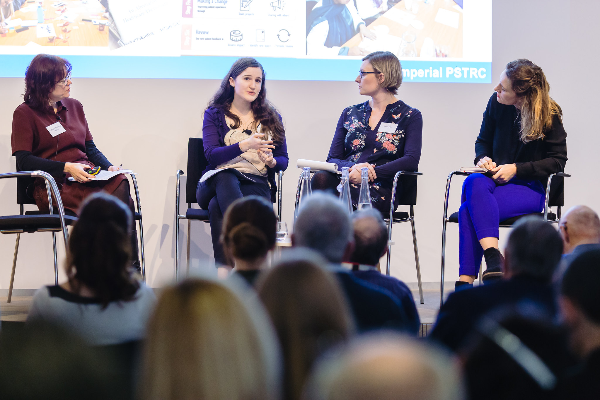 A photograph of an all-female panel discussing research involvement at a conference