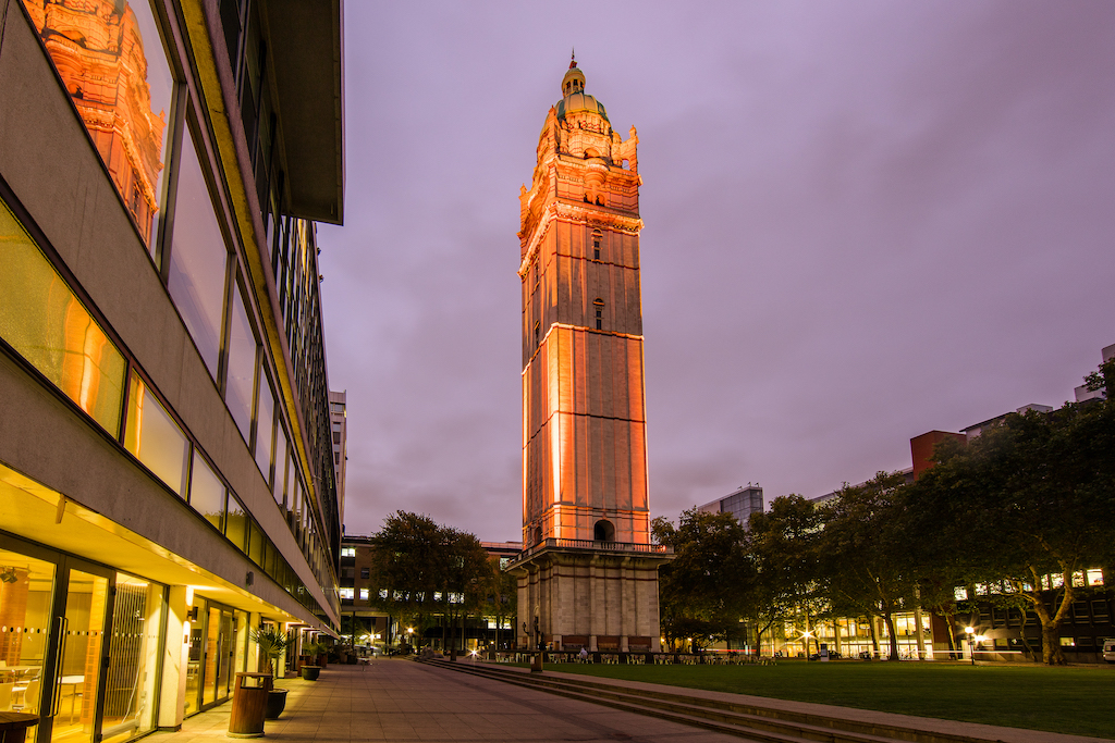 A photograph of Imperial's Queen's Tower light up in orange