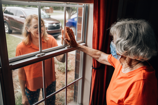 Woman with dementia reaching out to another woman through a window