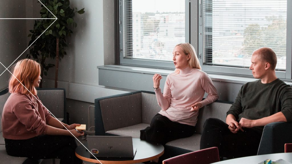 Two women and a man talking in a workplace