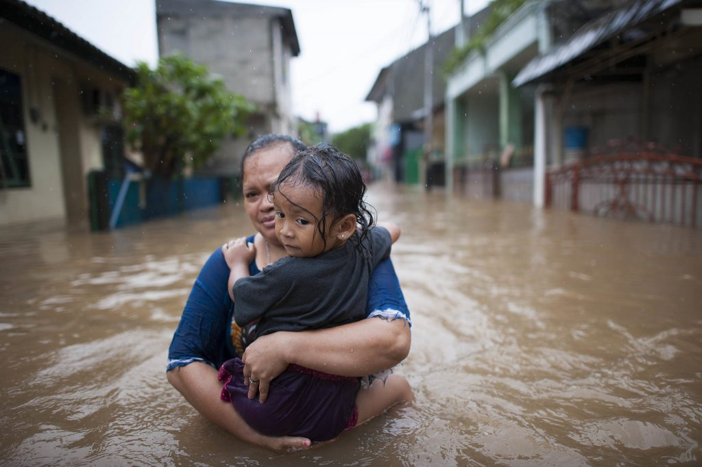 Woman carrying child in flood water due to climate change