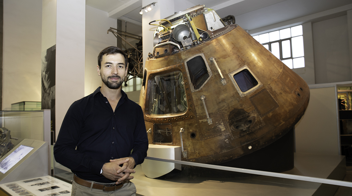 Dr Matthieu Komorowski in front of the Apollo 10 on display at the Science Museum. The spacecraft was used as the dress rehearsal for the actual Apollo 11 landing.