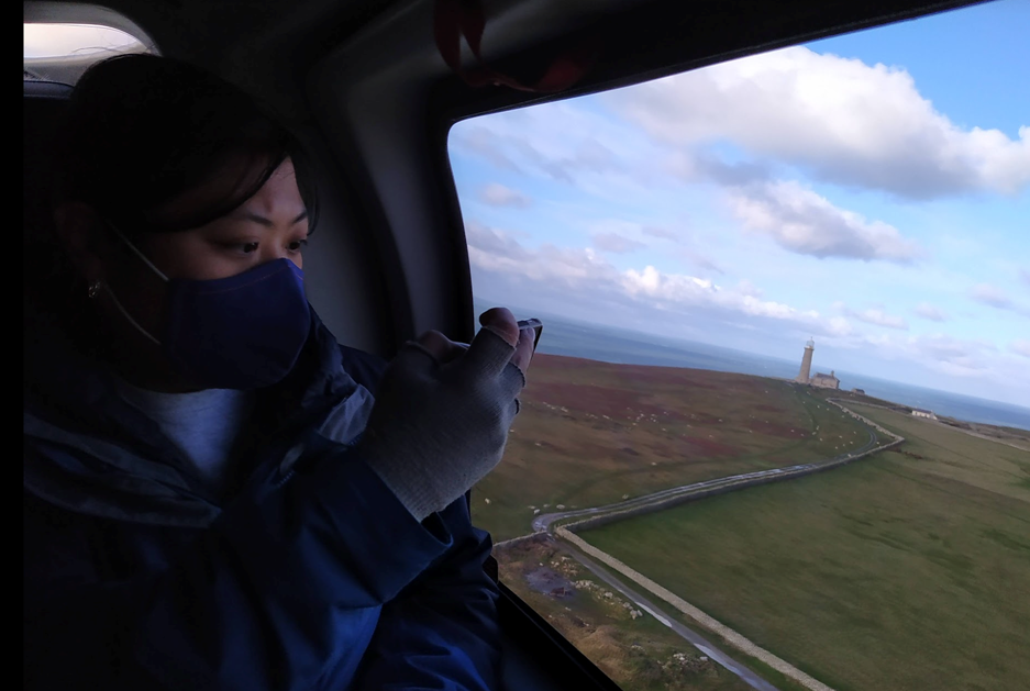 A student takes a photo of Lundy from the aerial view of the helipcopter