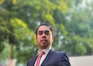 A photo of Leonardo Zea Reyes wearing a navy coloured suit with a pink tie and a background of green trees.