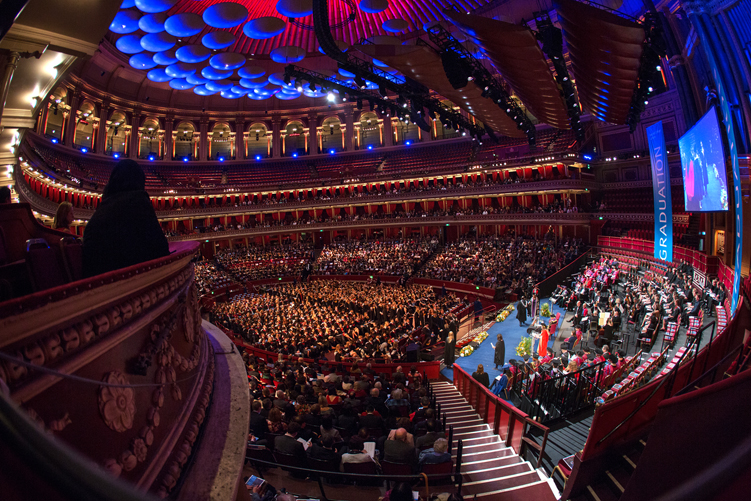 Professor Alice P. Gast shakes the hand of a Medicine Graduate on the stage at the Royal Albert Hall, while a spectator in a Niqab watches on from the left of the picture. Image copyright Thomas Angus / Imperial College London