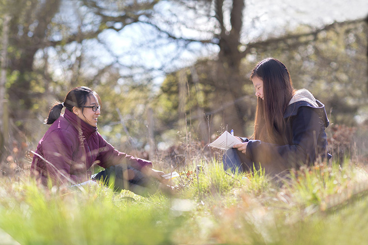 Two students sitting in a field and writing notes