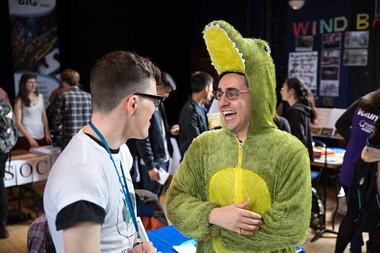 A student dressed in a crocodile costume laughs with a friend at the Freshers' Fair.