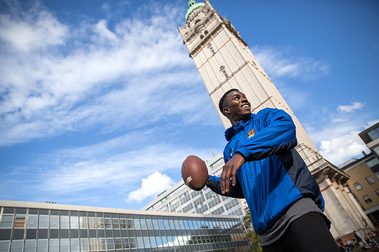 A student about to throw an American football, with the Queen's Tower in the background.