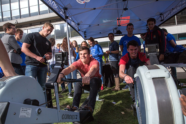 Two men using rowing machines and watched by other students.
