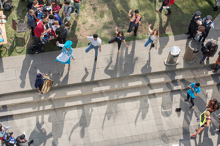 Five students dancing on the Queen's Lawn cast shadows across the terrace.