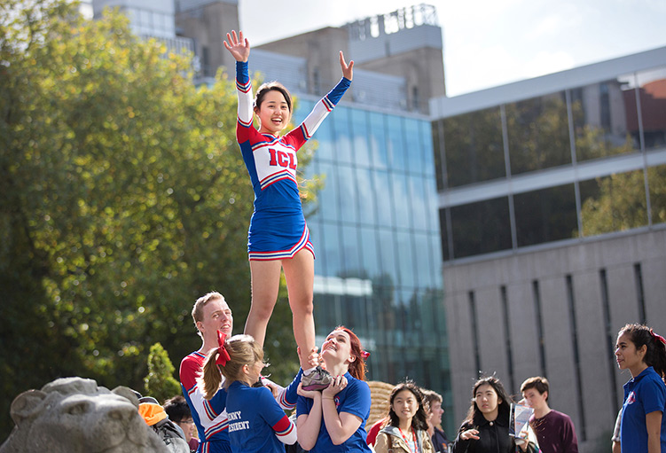 A cheerleader is held up in the air by three friends.